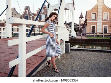 Young woman, brunette, curly hair wearing striped dress and sandals  posing on a pier against the background  of the city.