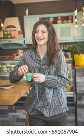 Young woman brunette drinking coffee in modern restaurant.