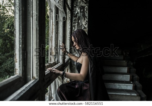 Young woman with brunette hair in black dress standing near the big vintage wooden window. Beautiful girl in the old, retro grunge abandoned derelict house building.