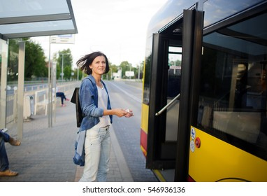 The young woman the brunette stands on the bus stop. She expects the bus. The woman is dressed in sports style. She high and slim. Behind shoulders at her a backpack.