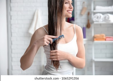 Young woman brushing hair after applying mask in bathroom