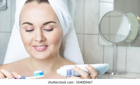 Young woman brushing her teeth. Happy young woman with a white towel on her head. The girl after a shower in a towel.