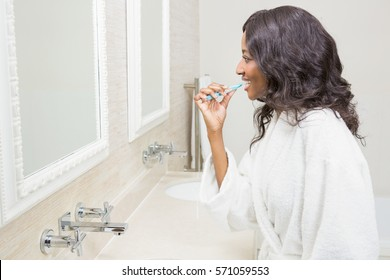 Young woman brushing her teeth in the bathroom