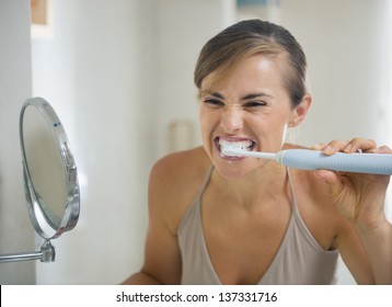 Young woman brushing teeth with grimace on face