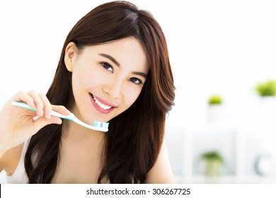 Young woman  brushing teeth in the morning