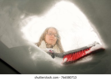 A young woman brusing snow off her windsheild looking from inside the car