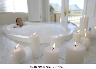 Young woman in bubble bath, illuminated candles in foreground