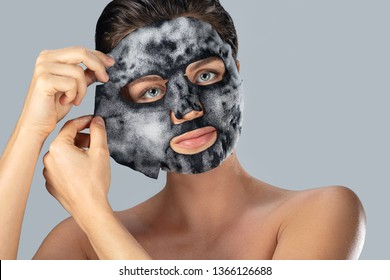 Young woman with  bubble sheet mask on her face on gray background