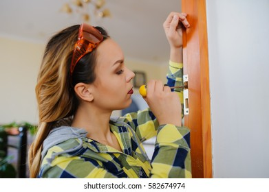 A young woman builder working using a screwdriver and fix the door. Orange protective glasses