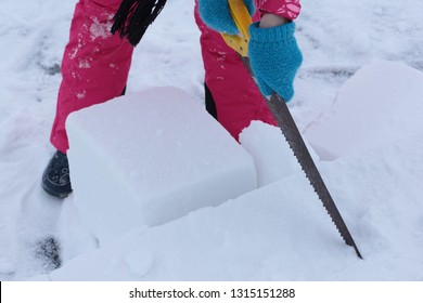 Young woman builds snow Igloo with snow blocks. Winter vacation. Winter and new year holidays