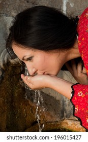 Young woman in bulgarian national dress drinking at an old well in the village of yeravna