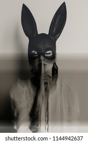 young woman in bunny mask showing quiet sign with her eyes closed