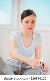 Young woman burning aromatic stick while sitting on the floor and relaxing