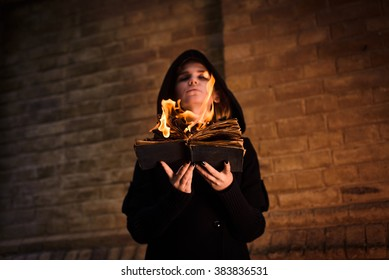young woman with burning book in hands