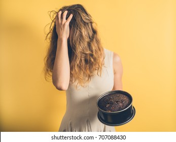 A young woman with a burnt cake is pulling her hair