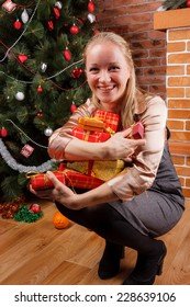 Young woman in business dress trying to hold big pile of Christmas presents