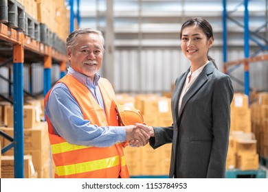 Young woman business owner shake hand with senior man. Asian people in suit and safety jacket with warehouse background. Successful logistic and warehouse business concept.
