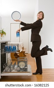 Young woman in a business suit loading the dishwasher in an exaggerated pose.