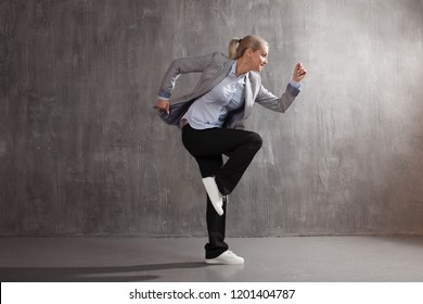 Young woman in business suit and sneakers. runner's pose, ready to run a long distance, concept business or startup