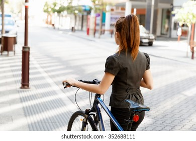 Young woman in business wear commuting on bicycle in city