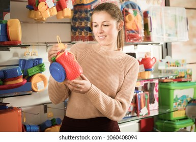 Young woman  buyer with children's plastic toys in the kids store