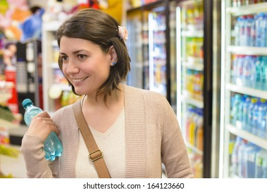 Young woman buying a bottle of water from a store