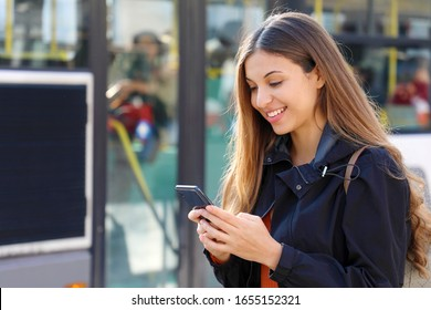 Young woman buying bus ticket online for city smart transportation. Happy beautiful student girl paying electronic ticket with smart phone app.