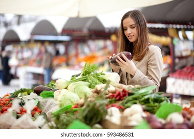 Young woman buying fresh vegetables at farmer's market