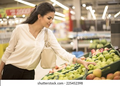 Young woman buying fruit at the market