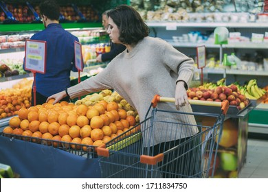 Young woman buying fruits in grocery store. Focused young woman standing with shopping trolley and choosing fresh oranges in supermarket. Shopping concept