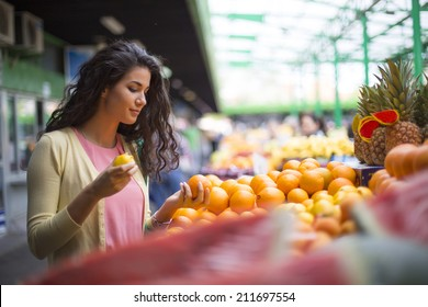 Young woman buying fruits at the market