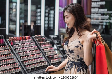 young woman buying lipstick in cosmetics store