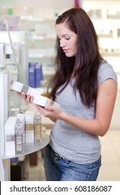 Young woman buying perfume in a beauty store