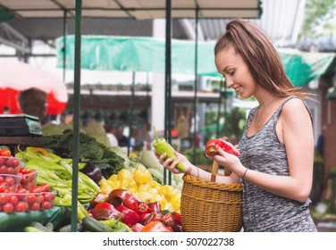 Young woman buying vegetables and fruits at local food market.