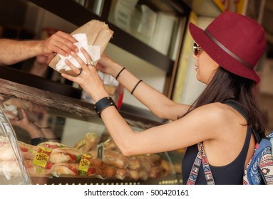 Young woman buys fresh pastries at bakery market on the street. Bakery product