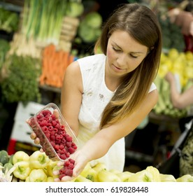 Young woman buys raspberries at the market