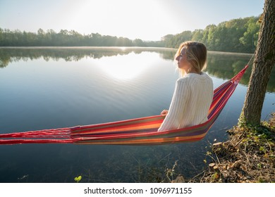 Young woman by the lake hanging on hammock relaxing in the morning. People relaxation travel concept.