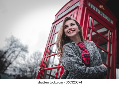 Young woman by red phone booth. Portrait of beautiful smiling happy young female casual woman standing in London, England, Great Britain.