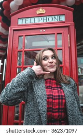 young woman by red phone booth. portrait of beautiful business young female in casual style standing in London, England, Great Britain