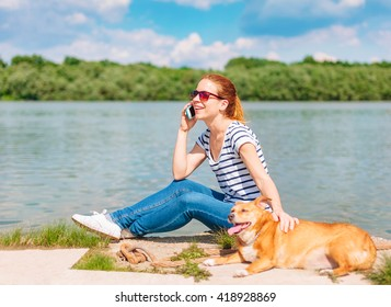 Young woman by the river talking on a cell phone in company with her dog