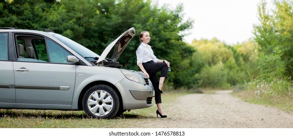 Young woman by the roadside after her car has broken down She opened the hood to see the damage.