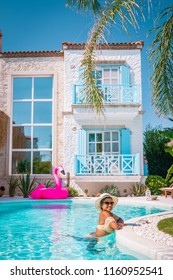 young woman by the swimming pool with flamingo, Alacati colorful house Turkey