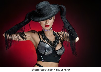 A young woman from a cabaret in a silvery bra, a black hat and long velvet gloves, dances on a black background