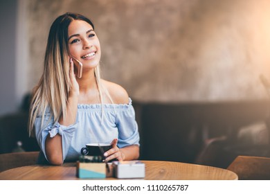 Young woman at cafe drinking coffee and talking on mobile phone