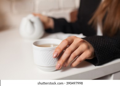 Young woman in cafe drinking here favorite beverage tea in white cup