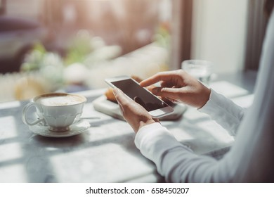 Young woman in a cafe reading a text message from her mobile phone, Bisness woman using smart phone during lunch time
