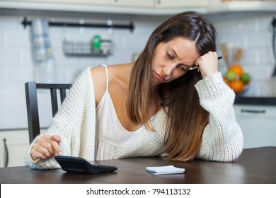 Young woman calculating her domestic budget in kitchen. Financial problems concept