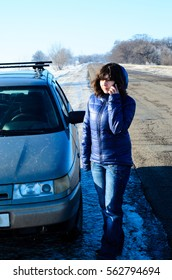 Young woman call for help near the broken car on roadside
