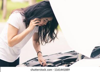 Young woman is calling to car mechanic to repair broken car.