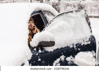 Young woman calling for help or assistance inside snow covered car.  Engine start in frost. Breakdown services in the winter.